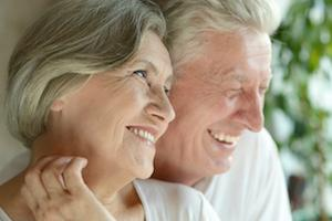 older couple looking onward with bright smiles I dental implants in apex nc