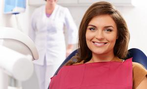 dental patient sitting in dental chair with bright smile I peridontal treatment at olive chapel family dentistry