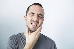 Man holding his jaw in pain in need of a root canal in Apex NC