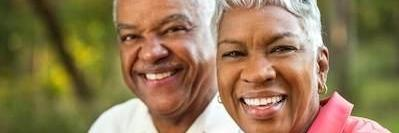 Older couple smiling after gum disease treatment in Apex NC