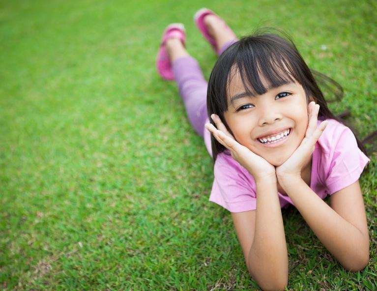 Girl posing in grass | Children's dentist Apex, NC